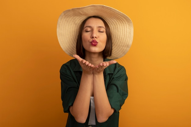 Pleased pretty caucasian woman with beach hat sends kiss with two hands on orange