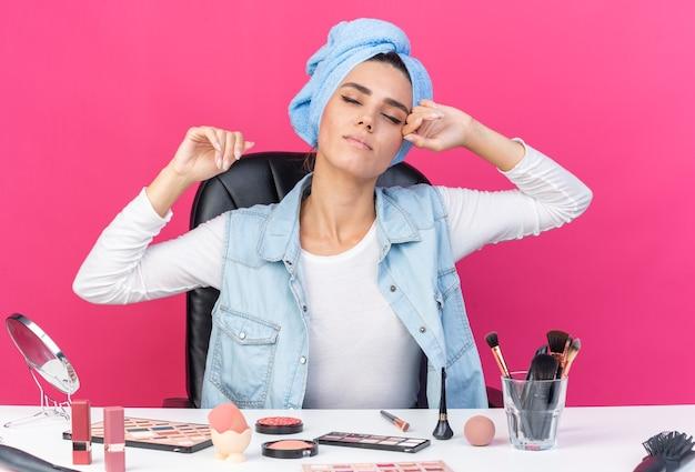 Довольная красивая кавказская женщина с обернутыми волосами в полотенце сидит за столом с инструментами для макияжа, поднимая руки вверх изолированной на розовой стене с копией пространства