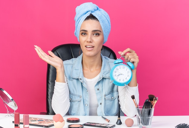 Pleased pretty caucasian woman with wrapped hair in towel sitting at table with makeup tools holding alarm clock