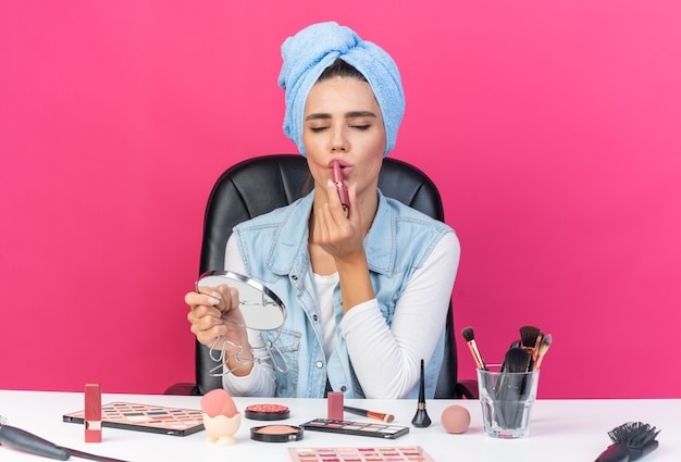 Donna abbastanza caucasica contenta con i capelli avvolti in un asciugamano seduto al tavolo con strumenti per il trucco che tiene lo specchio e applica il rossetto isolato sulla parete rosa con spazio di copia