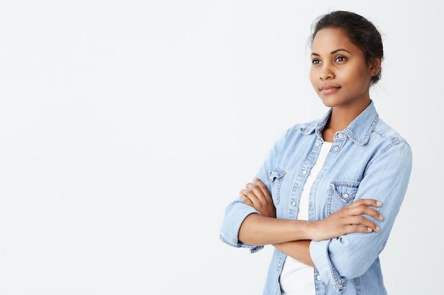 かなり暗い肌の黒髪の女性、黒い目は白いtシャツに身を包んだ、白い壁にポーズをとって手を組んで少し笑みを浮かべて手を繋いでいるデニムジャケット。人とライフスタイル