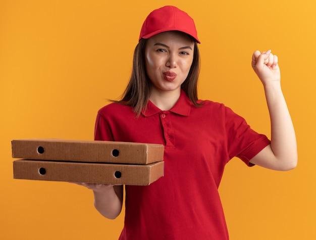 제복을 입은 만족스러운 예쁜 배달 여성이 주먹을 유지하고 오렌지에 피자 상자를 보유하고 있습니다.