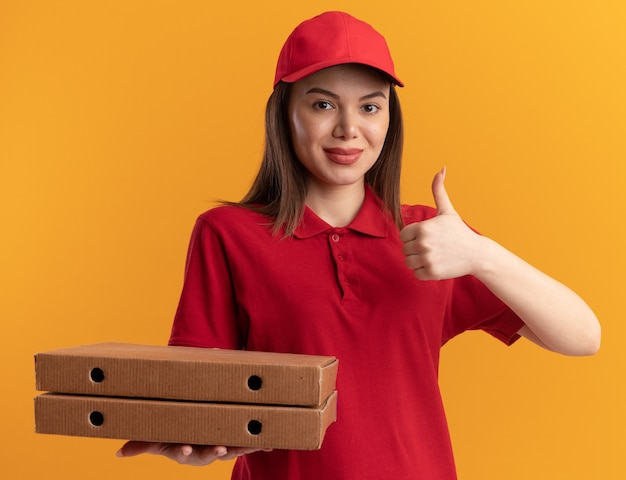 제복을 입은 예쁜 배달 여성이 엄지손가락을 치켜들고 주황색 벽에 피자 상자를 들고 복사 공간이 있습니다