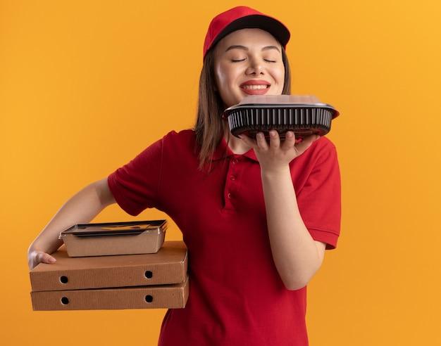 Piacevole donna delle consegne in uniforme tiene un pacchetto di cibo di carta su scatole per pizza e annusa il contenitore del cibo