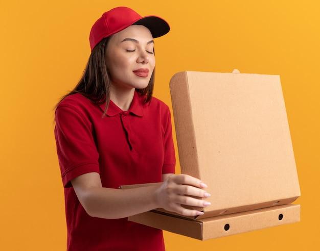 Piacevole donna delle consegne in uniforme tiene in mano scatole di pizza e fa finta di annusare