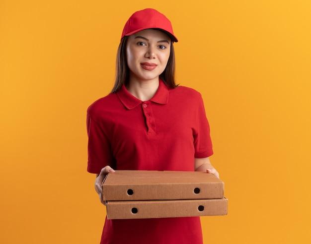 La graziosa donna delle consegne contenta in uniforme tiene le scatole della pizza