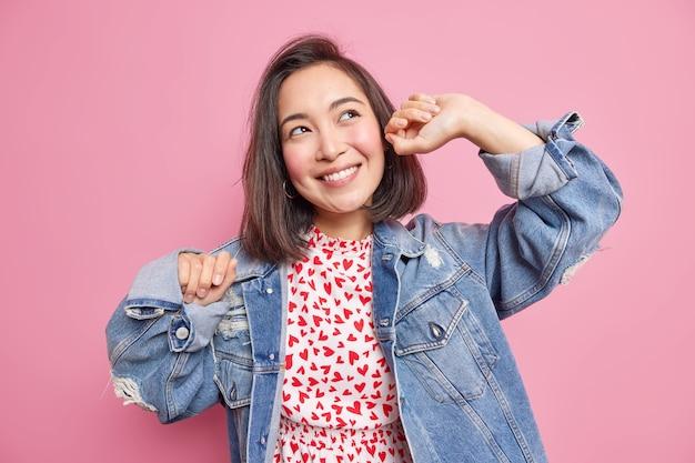 黒髪ののんきな表情で喜んでかなりファッショナブルな若い女性は、ピンクの壁に隔離されたファッショナブルなデニムジャケットに歯を見せて服を着た何かの笑顔についての腕の夢を上げます