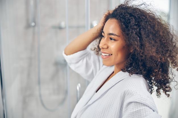 그녀의 곱슬 검은 머리를 만지고 목욕 가운에 기쁘게 예쁜 아가씨 프리미엄 사진