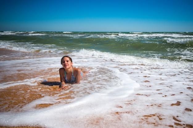 Довольная милая маленькая девочка наслаждается теплой морской водой, лежа на песчаном берегу в солнечный теплый летний день