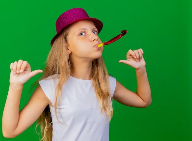 생일을 축하하는 휘파람을 불고 휴가 모자에 기쁘게 예쁜 소녀