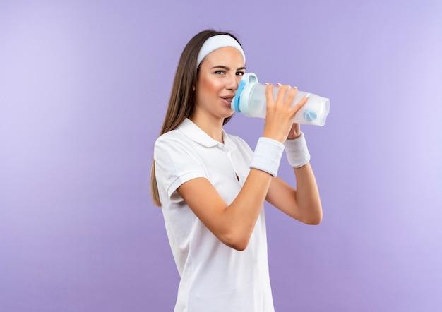 Довольная спортивная девушка с повязкой на голову и браслетом пьет воду, изолированную на фиолетовом пространстве