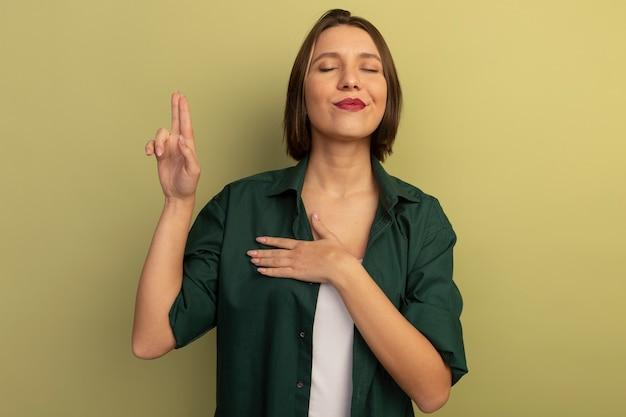 올리브 녹색 벽에 고립 된 맹세 제스처를 하 고 기쁘게 예쁜 여자