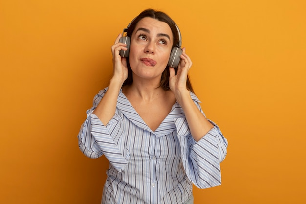Pleased pretty woman on headphones stucks out tongue and looks up isolated on orange wall