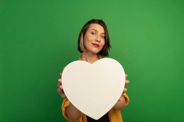 Donna graziosa soddisfatta che tiene forma del cuore isolata sulla parete verde