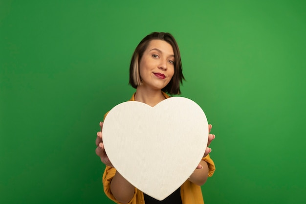 緑の壁に分離されたハートの形を保持している幸せなきれいな女性