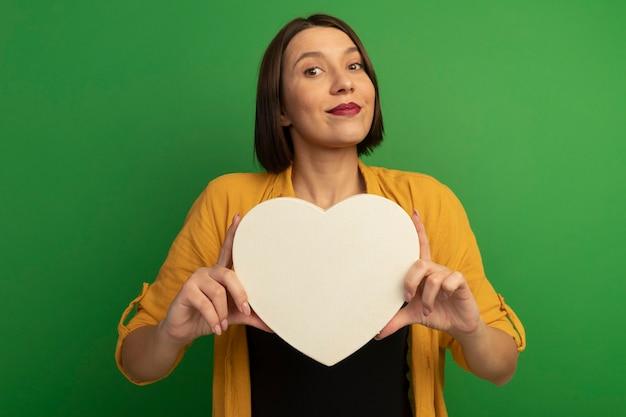La donna graziosa soddisfatta tiene la forma del cuore isolata sulla parete verde