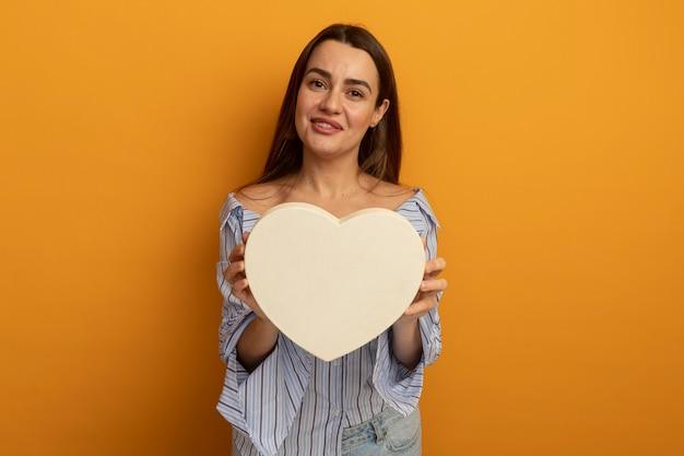 La bella donna soddisfatta tiene la forma del cuore isolata sulla parete arancione