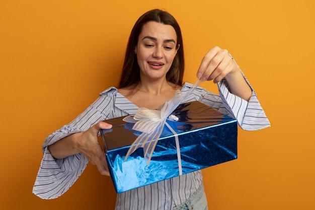 La donna graziosa soddisfatta tiene ed esamina la confezione regalo isolata sulla parete arancione