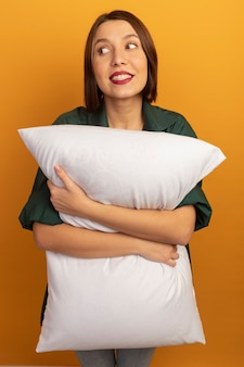 満足しているきれいな女性は枕を保持し、オレンジ色の壁に隔離された側を見て