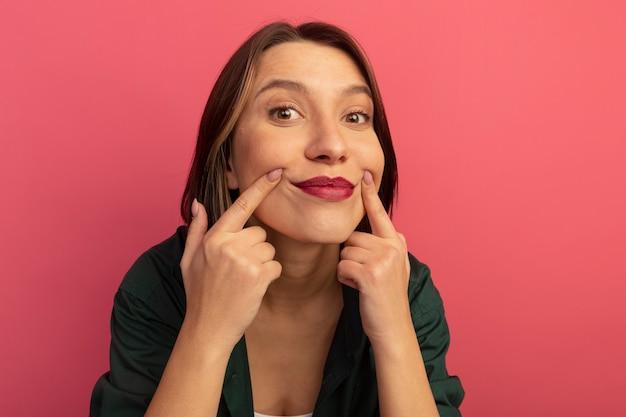 ピンクの壁に隔離された指で笑顔を保つ幸せなきれいな女性