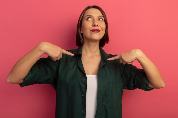 분홍색 벽에 고립 된 두 손으로 자신을 기쁘게 예쁜 여자 포인트