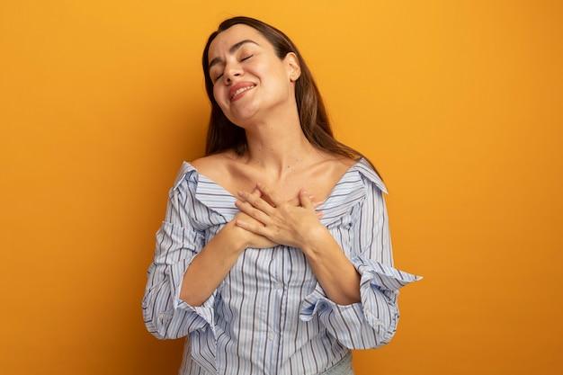 기쁘게 예쁜 여자는 오렌지 벽에 고립 된 가슴에 손을 넣습니다.