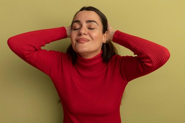 Felice bella donna sta con gli occhi chiusi tenendo la testa isolata sulla parete verde oliva