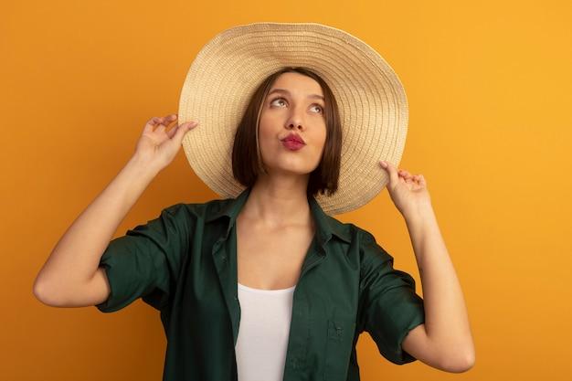 ビーチ帽子をかぶった幸せなきれいな女性はオレンジ色の壁に孤立して見上げる