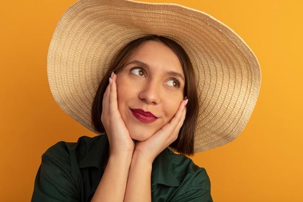 ビーチ帽子をかぶった幸せなきれいな女性は、オレンジ色の壁に隔離された顔に手を置きます