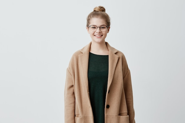 Pleased pretty woman with blonde hair in knot, eyeglasses and healthy skin dressed in brown coat over green sweater smiling while posing against concrete wall. people and lifestyle