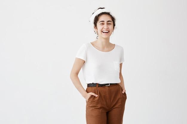 パンに黒くてウェーブのかかった髪、黒い目、白いtシャツに身を包んだ健康な肌、ポケットに手をつないだ茶色のズボンを着て、白い壁にポーズをとって満足しているきれいな女性。