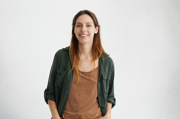 Pleased pretty woman with dyed hair, dark eyes and healthy skin dressed in brown t-shirt, green jacket holding hands in pockets smiling while posing against white concrete wall. people and lifestyle