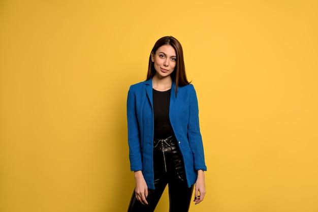 Felice bella donna con i capelli lunghi, gli occhi scuri e la pelle sana vestita giacca blu, sorridente mentre posa contro il muro di cemento giallo. persone e stile di vita