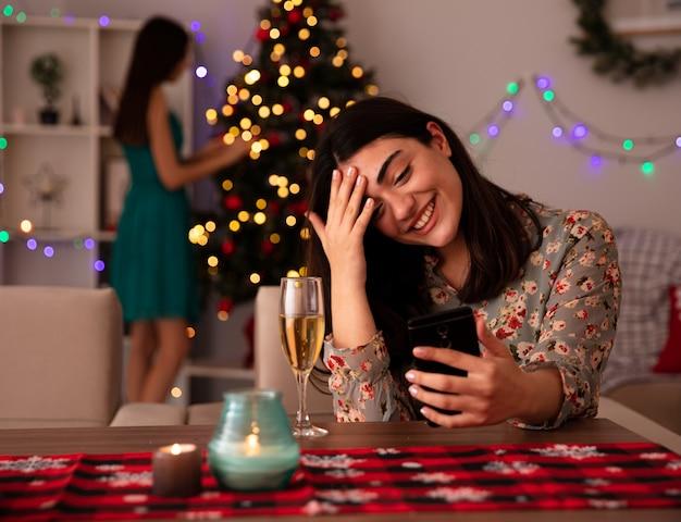 喜んでいるかわいい若い女の子がクリスマスツリーを飾り、彼女の友人は額に手を置き、テーブルに座って家でクリスマスの時間を楽しんでいる電話を見ます