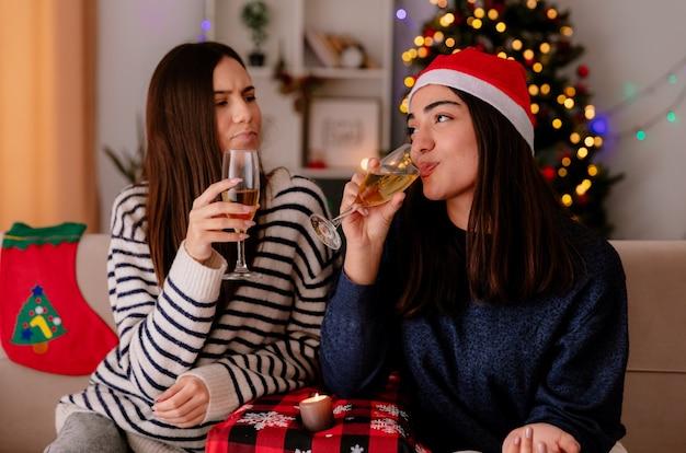 Soddisfatte ragazze graziose che bevono bicchieri di champagne seduti sulle poltrone e godersi il periodo natalizio a casa
