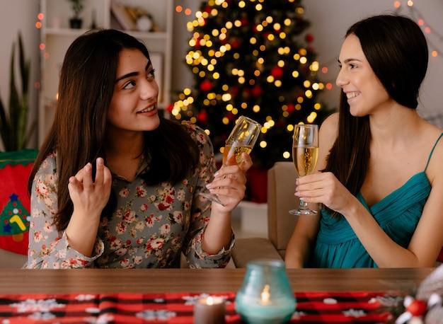 기쁘게 예쁜 젊은 여자가 테이블에 앉아 샴페인 잔을 들고 집에서 크리스마스 시간을 즐기고