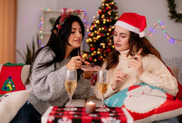 Довольные симпатичные молодые девушки держат кисти для пудры, делают макияж, сидя на креслах и наслаждаясь рождеством дома
