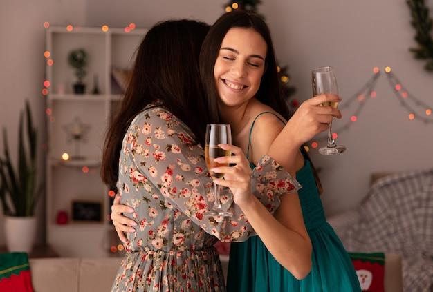 Compiaciute ragazze carine si abbracciano e tengono bicchieri di champagne godendosi il periodo natalizio a casa