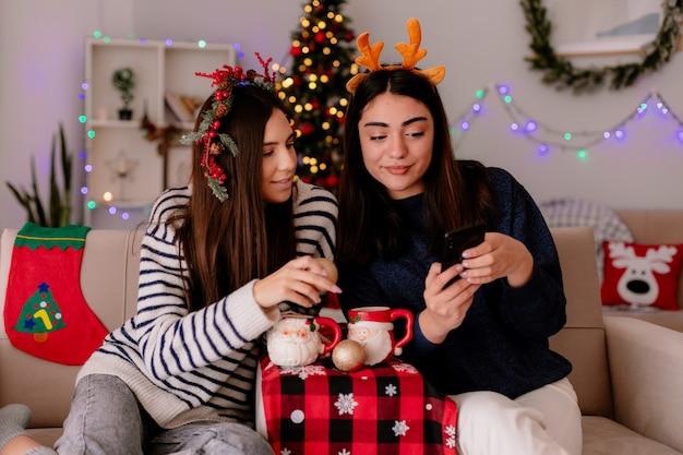 Довольные симпатичные молодые девушки с венком из падуба и ободком с оленями смотрят на телефон, сидя на креслах и наслаждаются рождеством дома