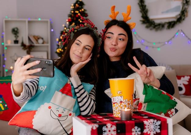 Довольные симпатичные молодые девушки с венком из падуба и ободком с оленями делают селфи, глядя в телефон, сидя на креслах и наслаждаясь рождеством дома