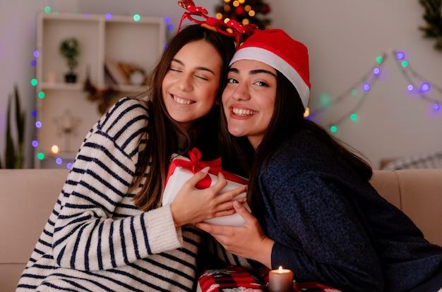 Le ragazze graziose soddisfatte con gli occhiali della renna e il cappello della santa tengono il contenitore di regalo di natale che si siedono sulle poltrone e si godono il periodo natalizio a casa