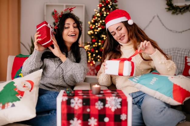 サンタの帽子とヒイラギの花輪を持つ満足しているかなり若い女の子は、アームチェアに座って、家でクリスマスの時間を楽しんでいるギフトボックスを保持します