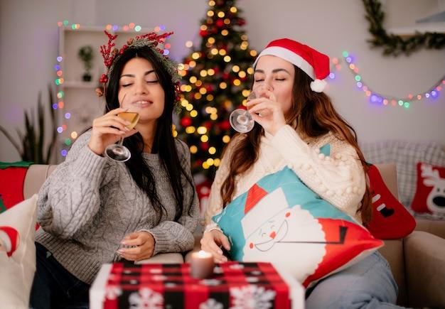 Le ragazze graziose e contente con il cappello di babbo natale bevono bicchieri di champagne seduti sulle poltrone e si godono il periodo natalizio a casa