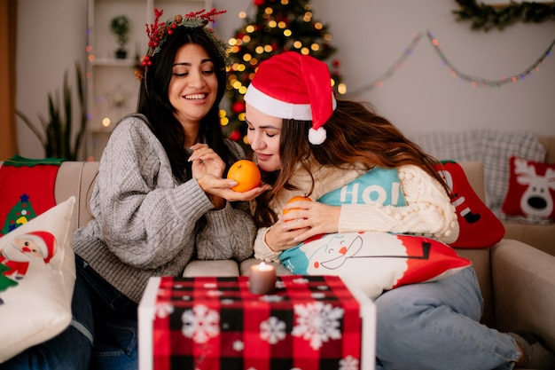 Pleased pretty young girls with santa hat hold and sniff oranges sitting on armchairs and enjoying christmas time at home