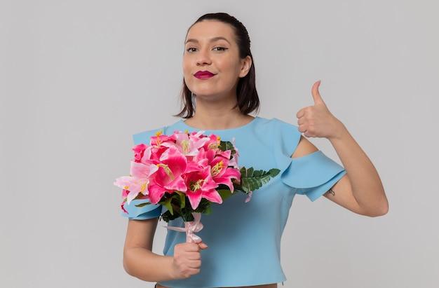 Una bella giovane donna contenta che tiene in mano un mazzo di fiori e fa il pollice in alto
