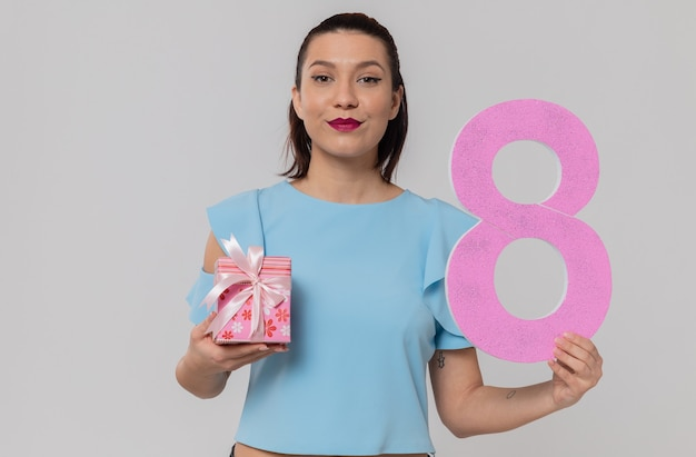 ピンクの8番とギフトボックスを持って満足しているかなり若い女性