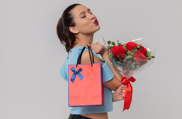 Pleased pretty young woman standing sideways with closed eyes holding bouquet of flowers and gift bag