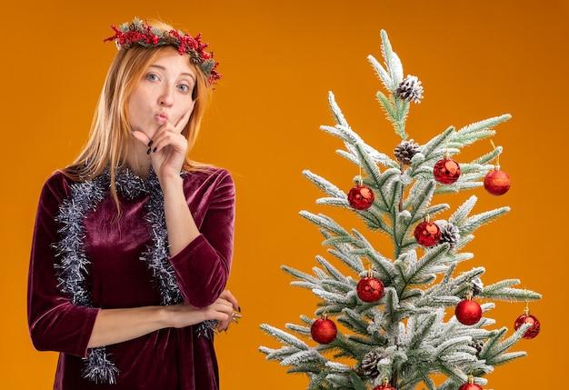 オレンジ色の背景で隔離の頬に指を置く赤いドレスと花輪を首に花輪を身に着けているクリスマスツリーの近くに立っている唇をすぼめる若い美しい少女を喜んで