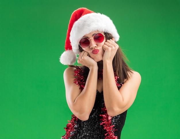 녹색 벽에 고립 된 뺨에 손을 댔을 목에 갈 랜드와 함께 크리스마스 모자와 안경을 쓰고 기쁘게 pursing 입술 젊은 아름 다운 소녀