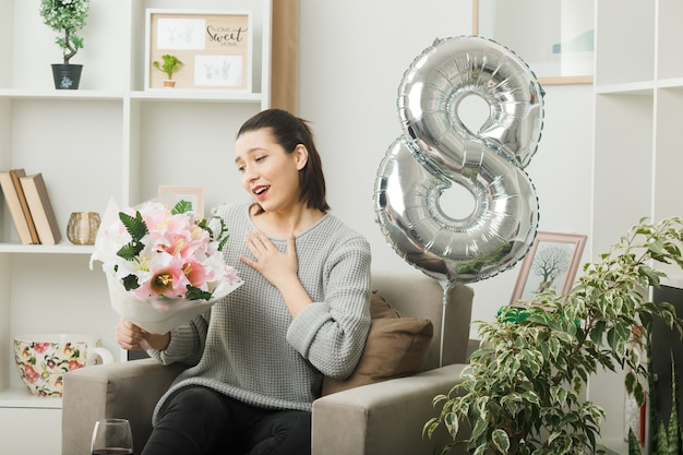 Pleased putting hand on heart beautiful girl on happy women day holding and looking at bouquet sitting on armchair in living room